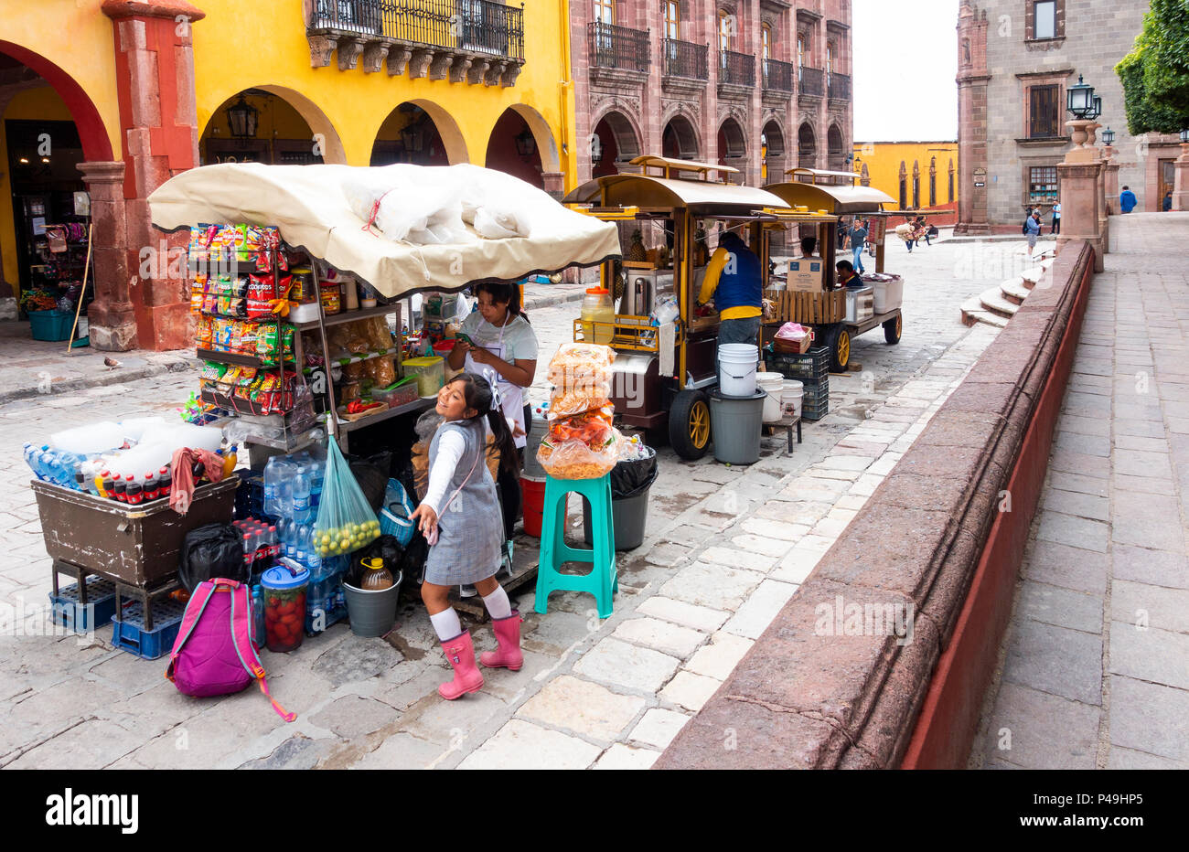 Young girl dancing at her mother's food carts next to La Jardin inSan Miguel de Allende in central Mexico - Stock Image