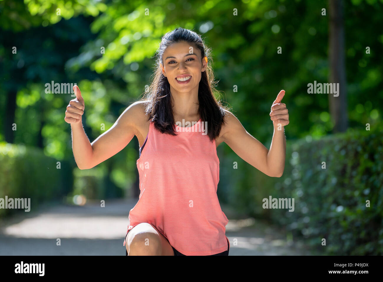 0003ba8982dda Summer portrait of sportive latin girl in pink tank top showing a thumb up  cheerfully smiling