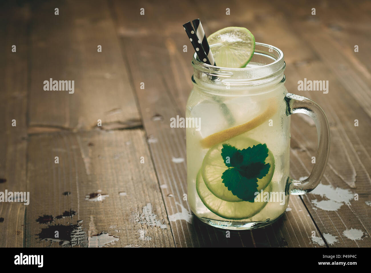 Cold Mojito Cocktail with Ice, Lemon and Mint Leaves in Mason Jar on Rustic Dark Wooden Background as Summer Concept - Stock Image