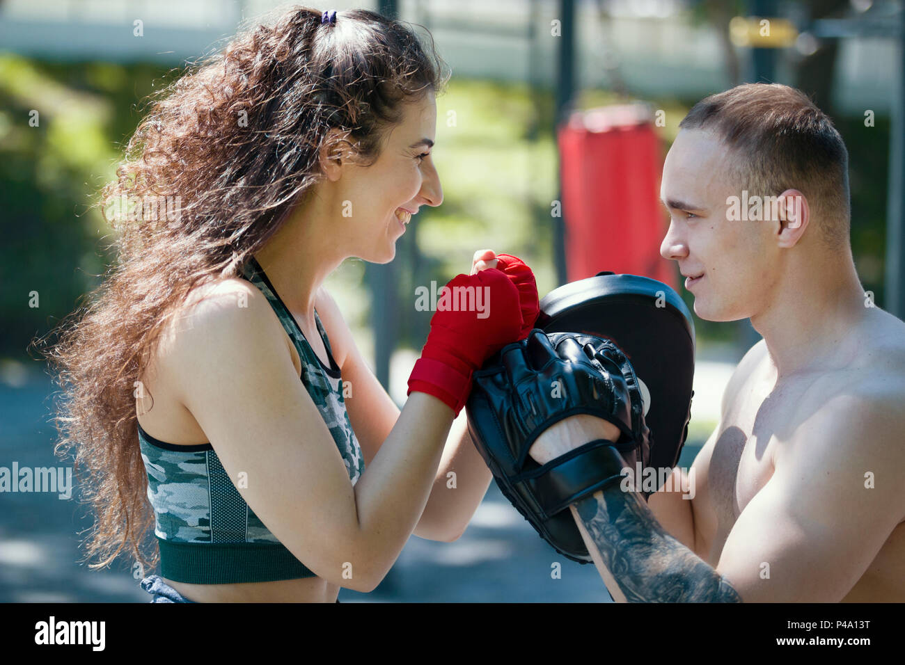 Portrait of young lovely couple looking into each other's eyes in boxing workout - Stock Image