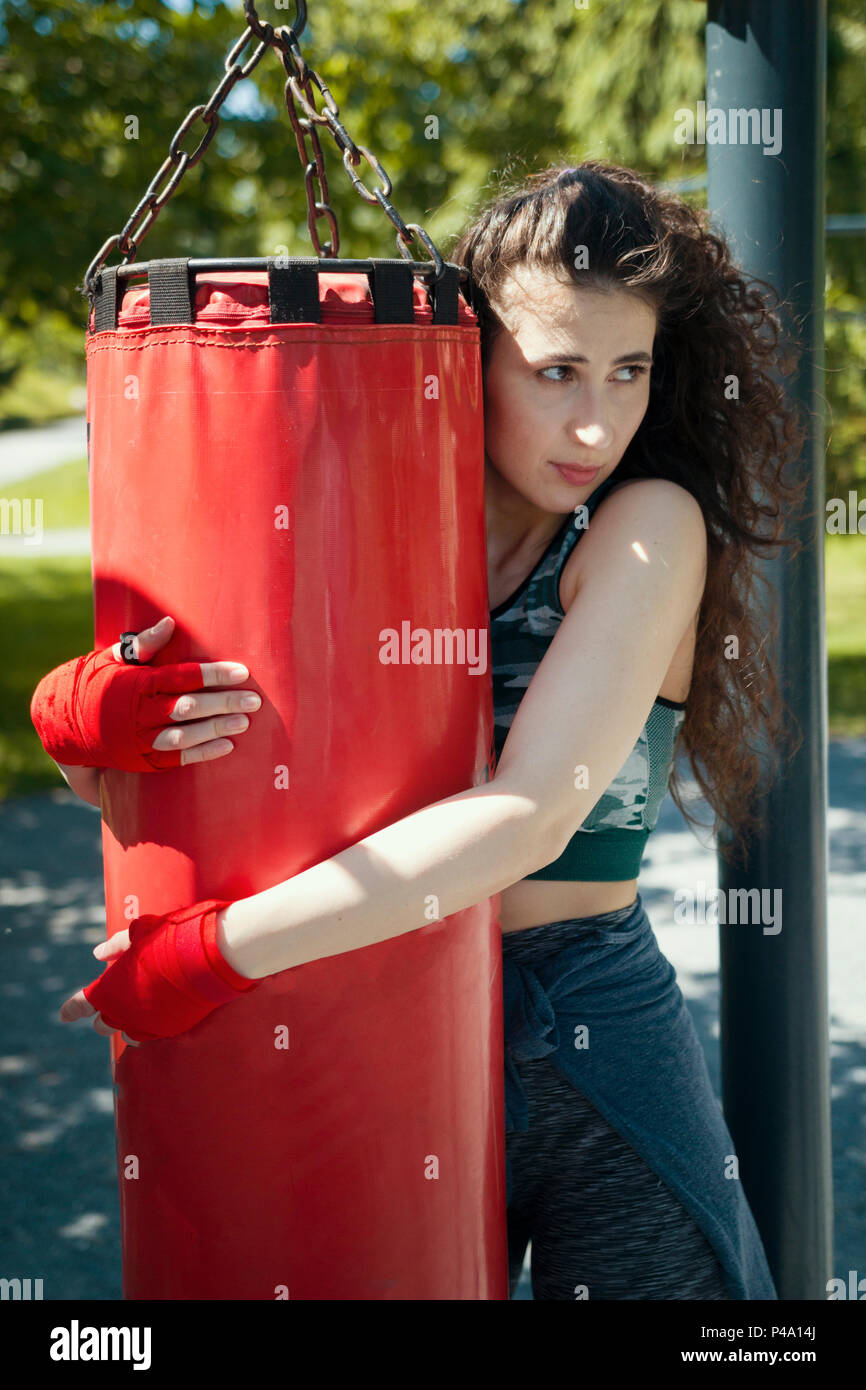Portrait of young woman in sportswear hugging the punching bag - Stock Image