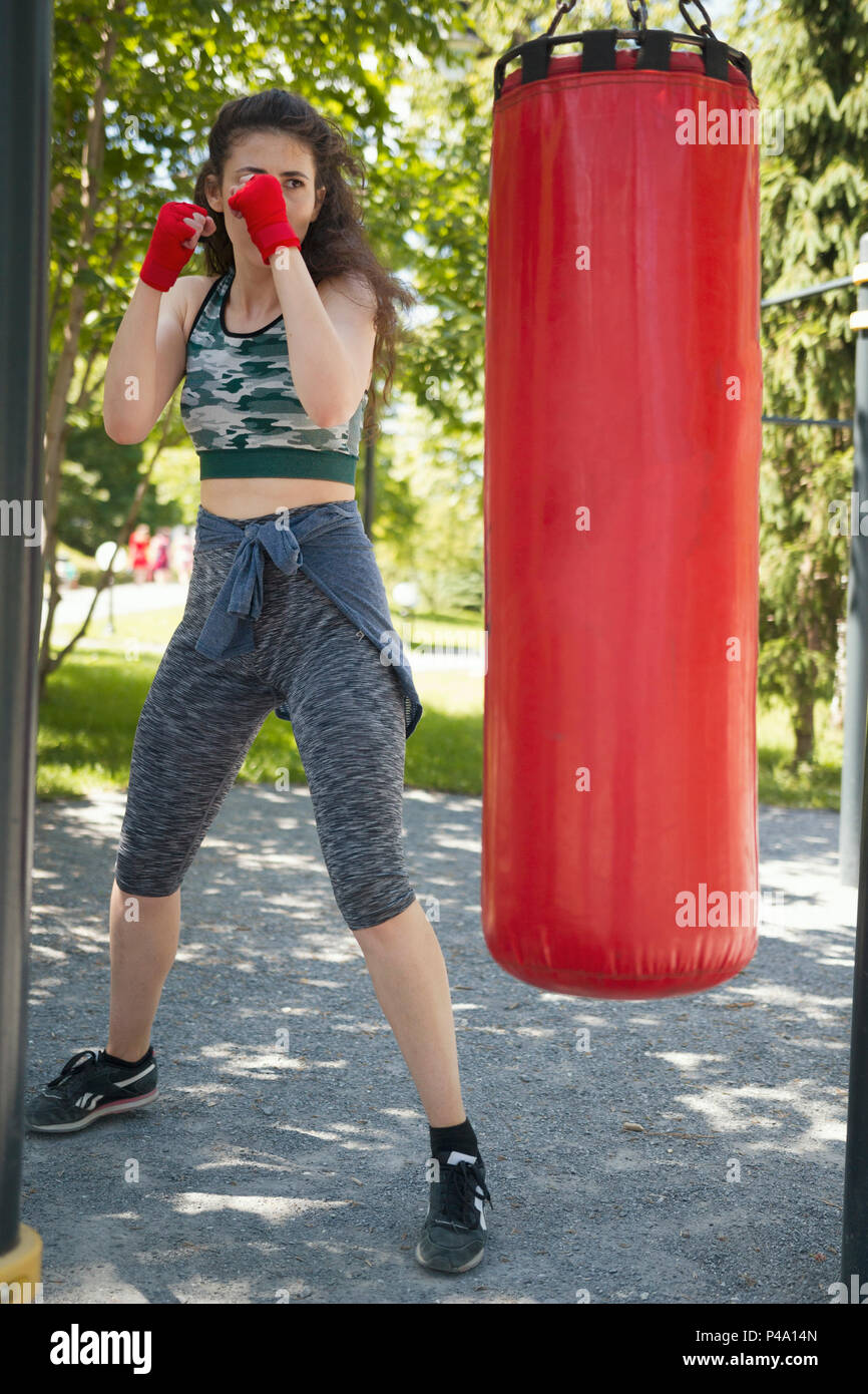 Attractive young woman in sportswear beats a punching bag - Stock Image