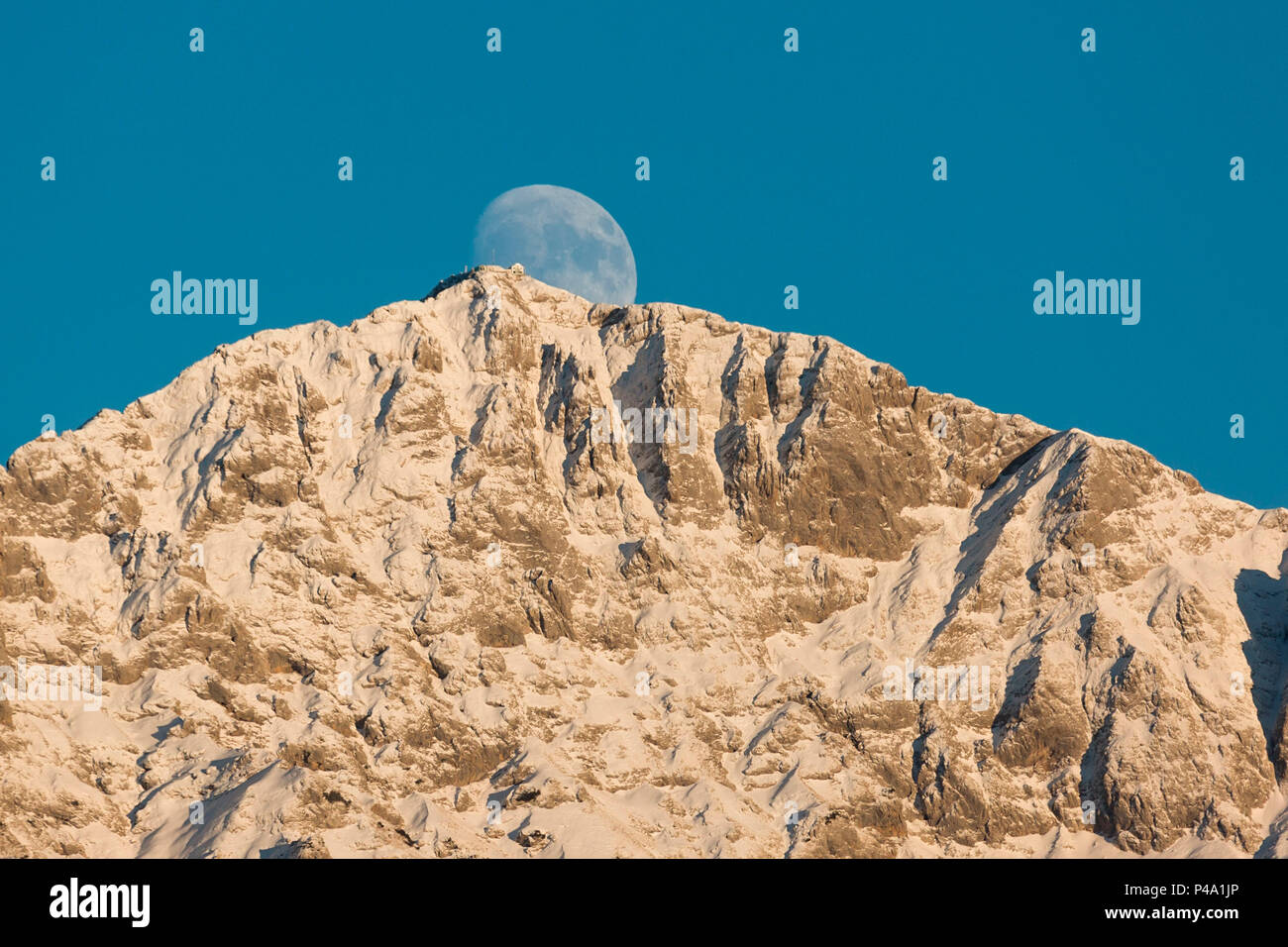 Full Moon rising behind the summit of Grigna Settentrionale and its refuge Rifugio Brioschi, province of lecco, lombardy, italy - Stock Image