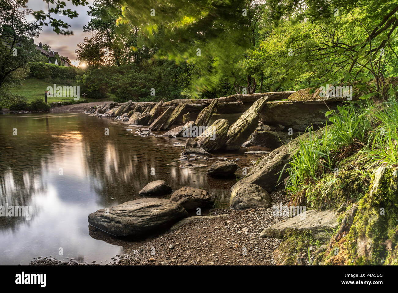 Tarr Steps Exmoor, UK. 21st June, 2018. UK Weather -June 21st, the longest day, the wind strengthens at dawn clearing the cloud allowing the sun to light up the historic Tarr Steps on the River Barle in Exmoor National Park in Somerset. Credit: Terry Mathews/Alamy Live News - Stock Image