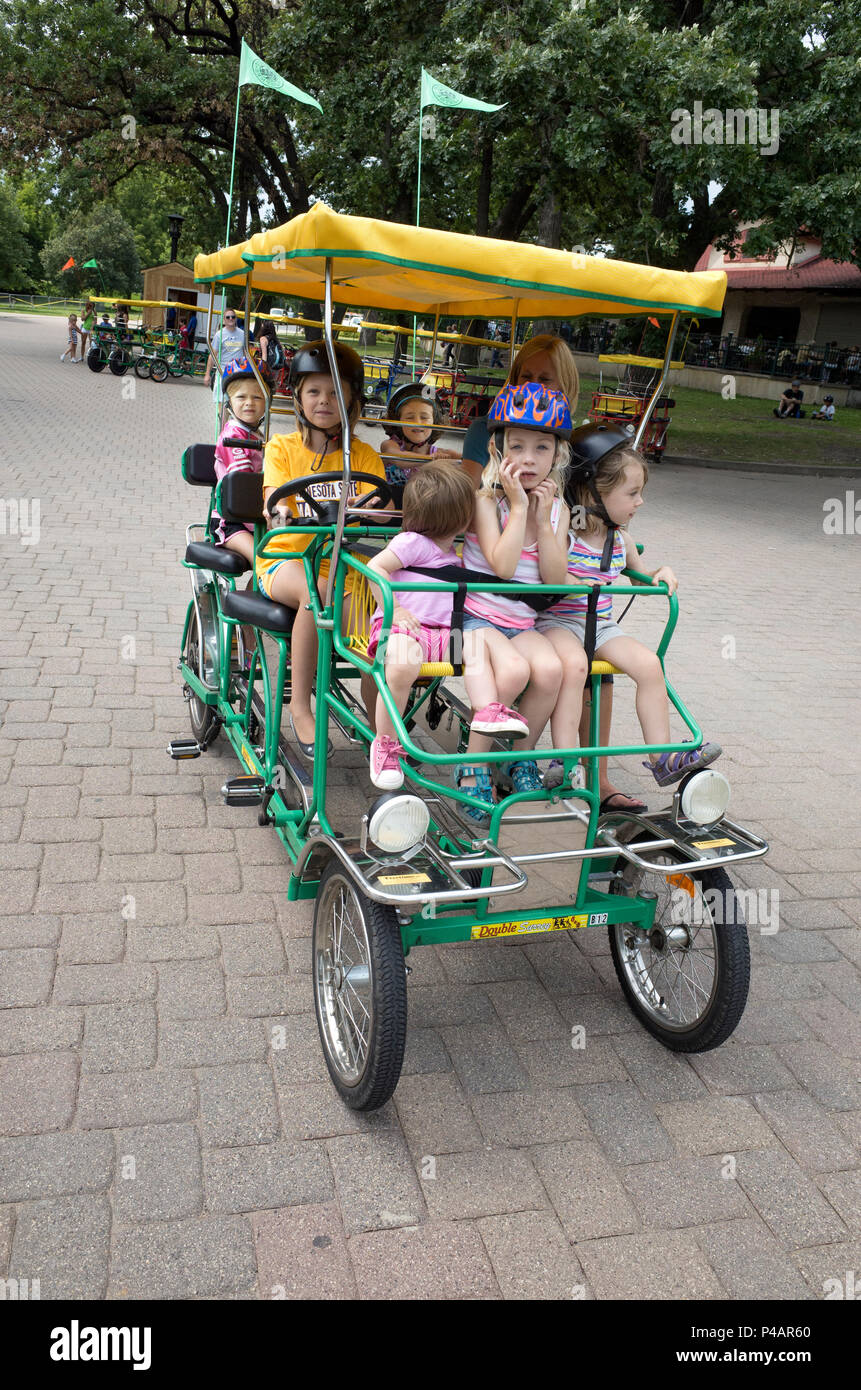 Mom and children peddling a self propelled double surrey at Minnehaha Park. Minneapolis Minnesota MN USA - Stock Image