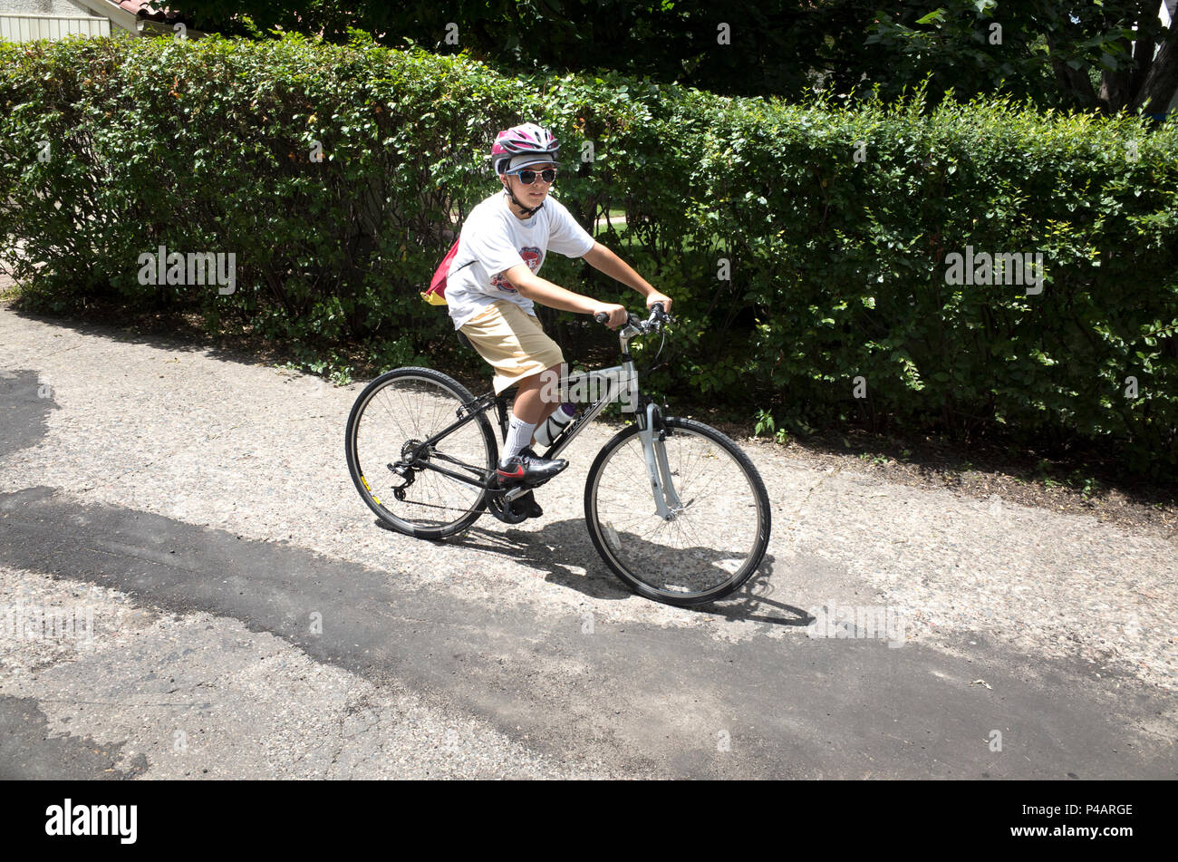 Cool looking preteen age 12 tooling down the alley wearing sun glasses and helmet waiting to start a good bicycle trip. St Paul Minnesota MN USA - Stock Image