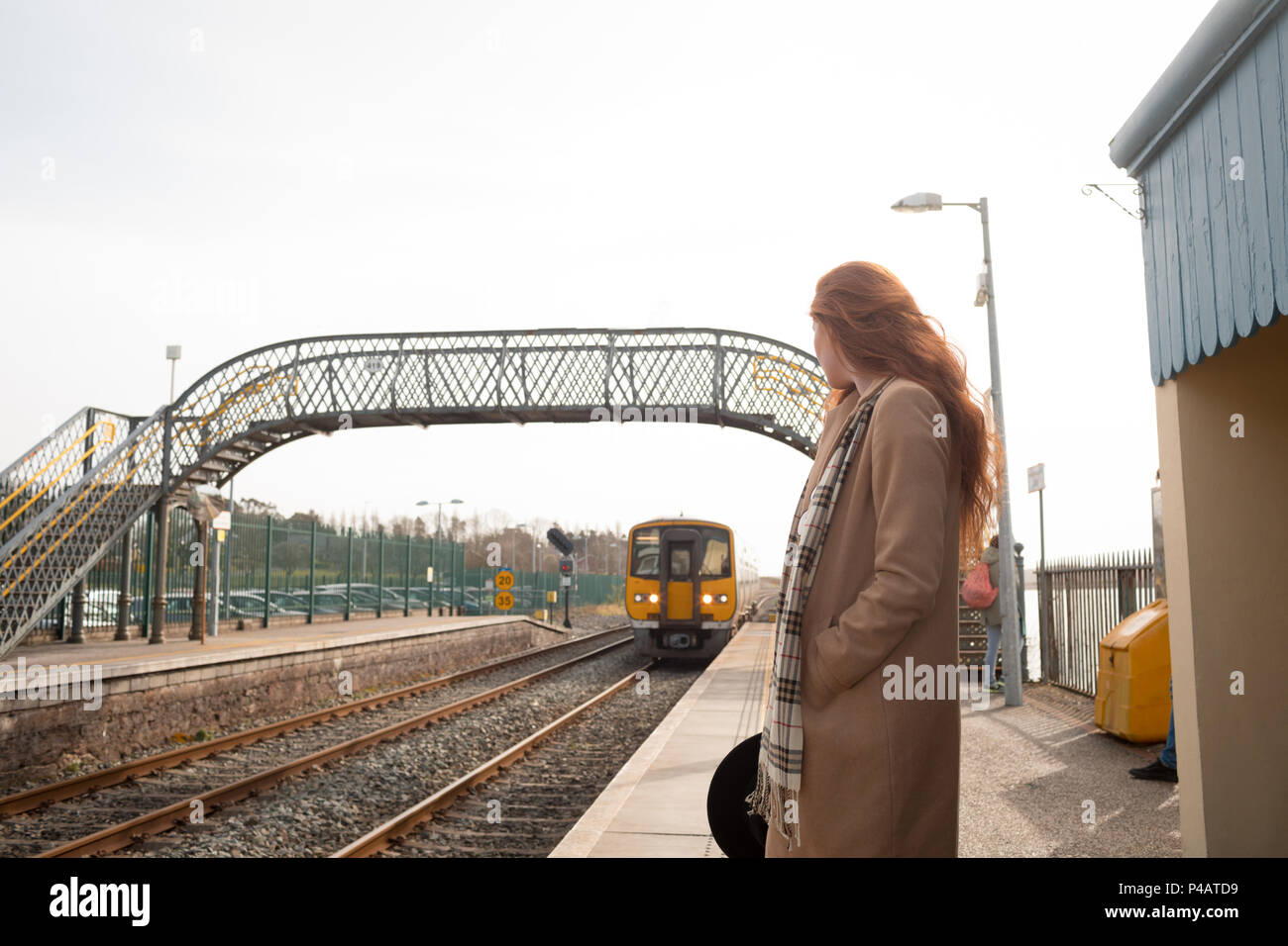 Woman standing at railway station - Stock Image