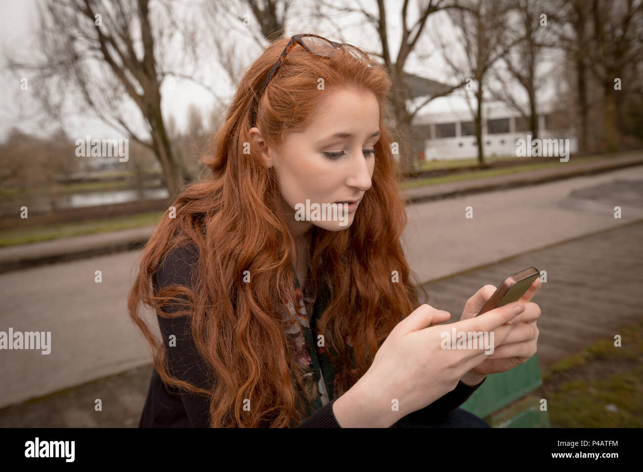 Woman using mobile phone in countryside - Stock Image