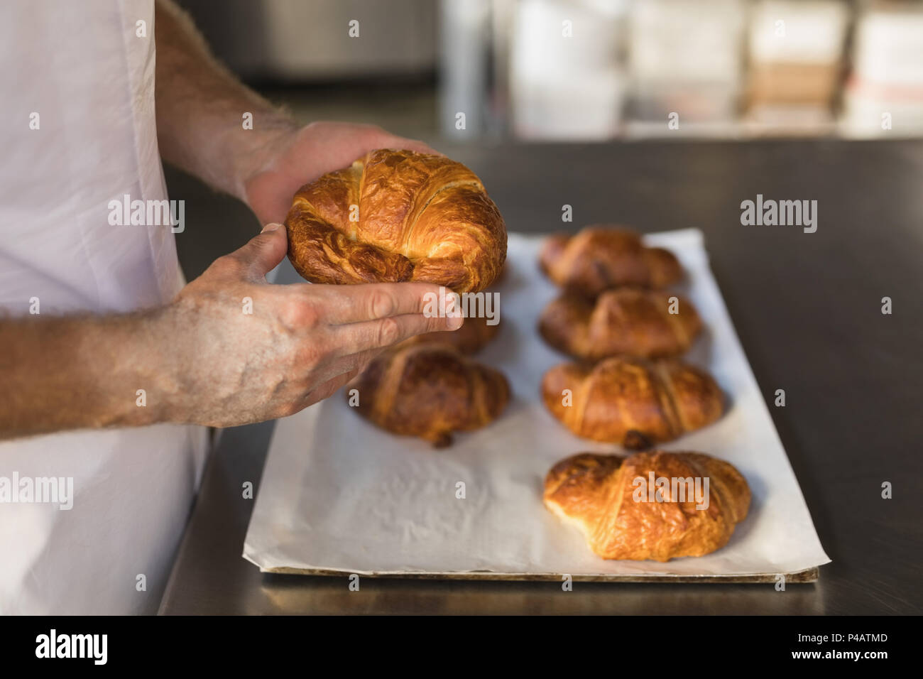 Male baker holding baked crescent rolls in bakery shop - Stock Image