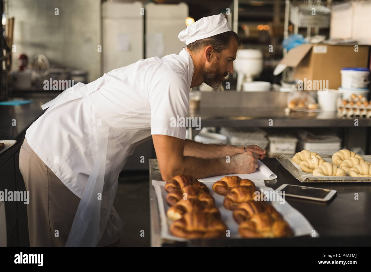Male baker working in baker shop - Stock Image