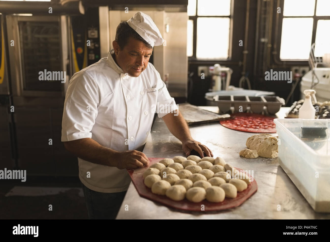 Male baker with dough balls in bakery shop - Stock Image