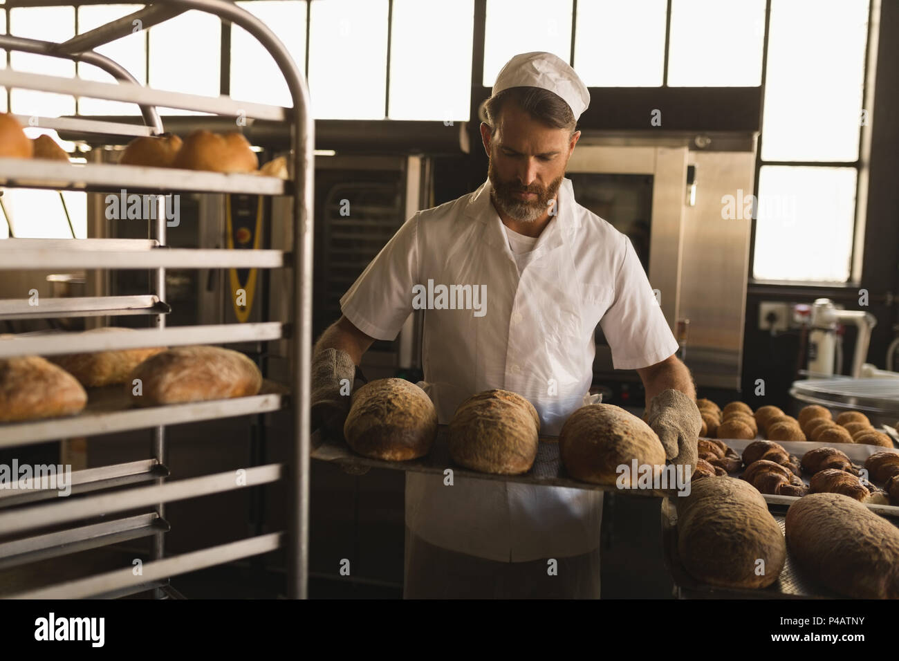 Male baker holding a tray of baked breads - Stock Image