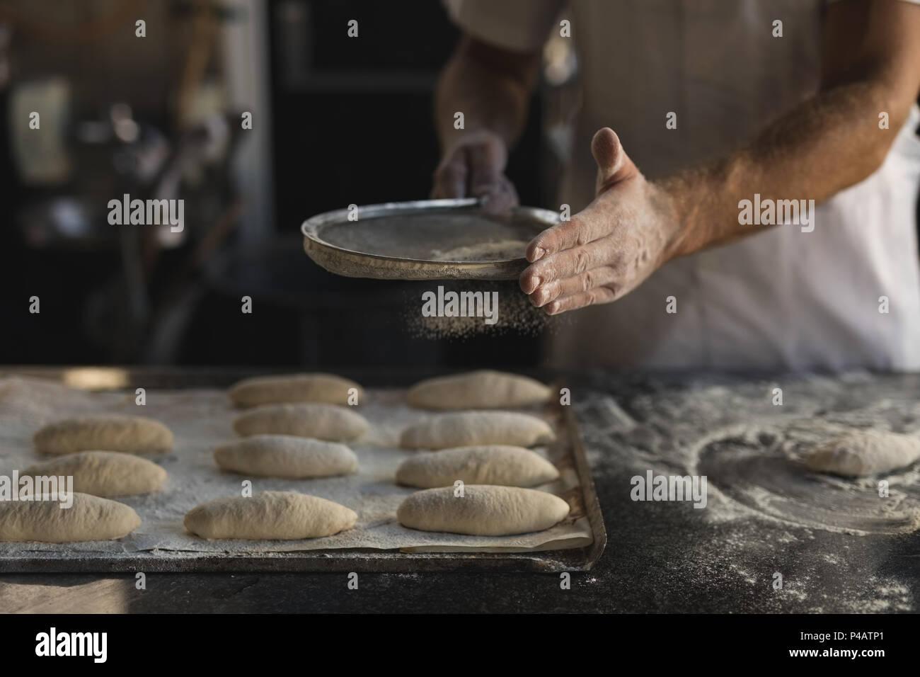 Male baker preparing dough in bakery shop - Stock Image