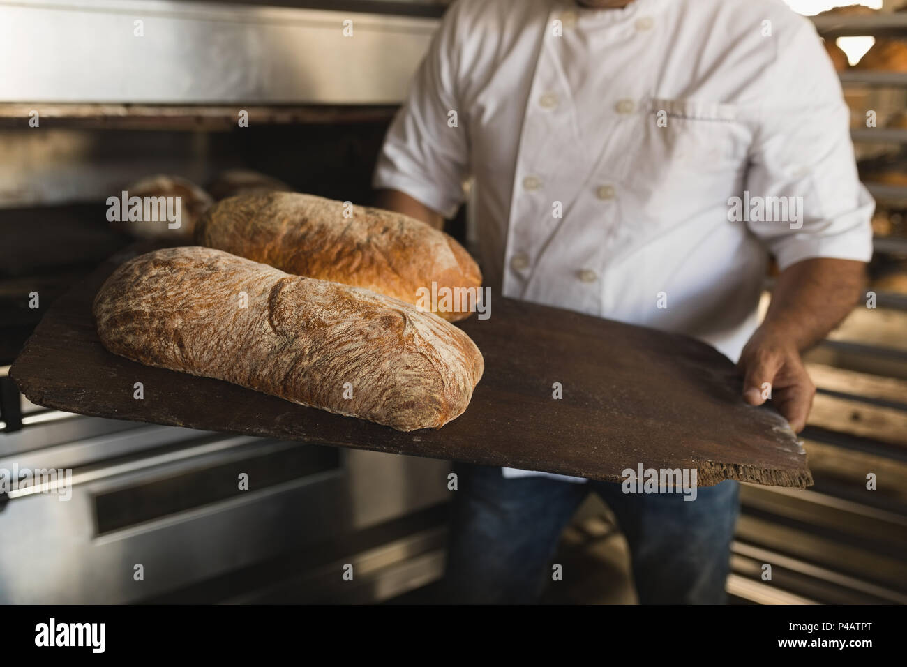 Male baker holding baked bread in bakery shop - Stock Image