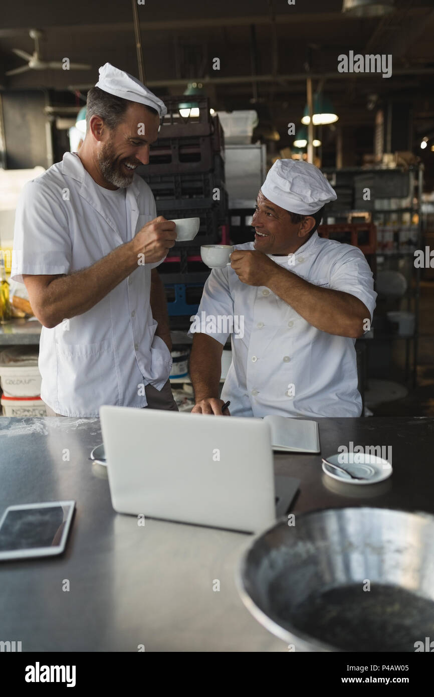 Male baker having coffee with his coworker - Stock Image