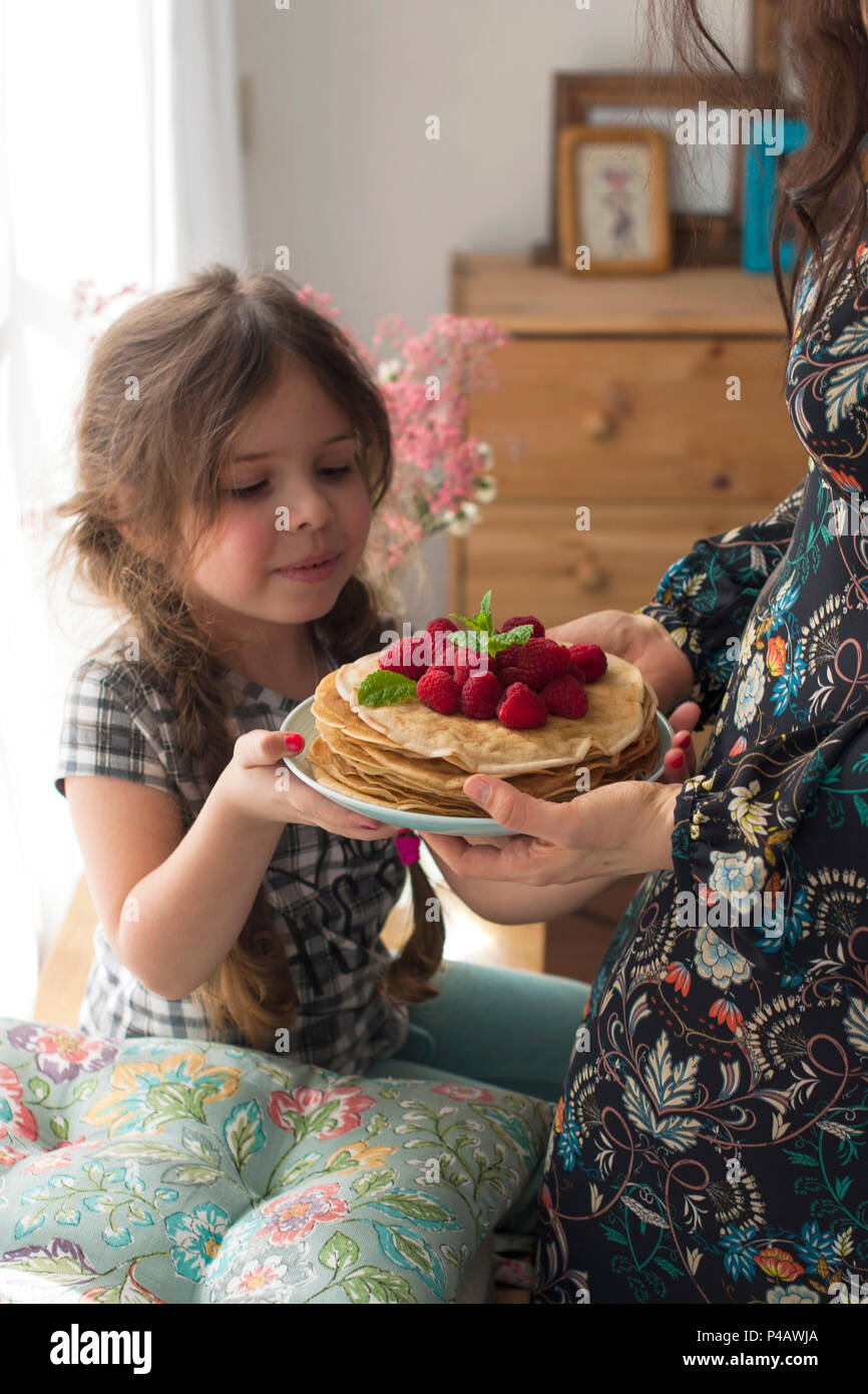 Mom and the girl are holding a plate with homemade pancakes and berries. Delicious breakfast at home. A happy family. Good morning. - Stock Image