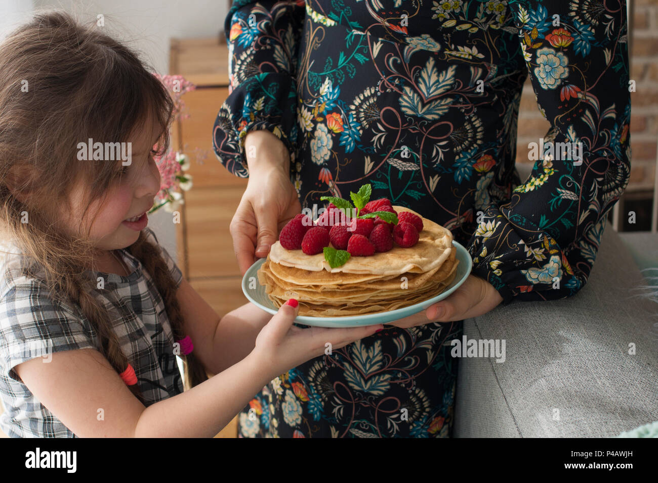 Mom and the girl are holding a plate with homemade pancakes and berries. Delicious breakfast at home. A happy family. Good morning, - Stock Image
