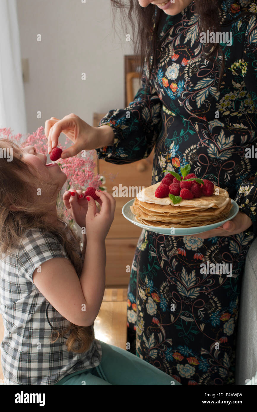 Mom and the girl are holding a plate with homemade pancakes and berries. Delicious breakfast at home. A happy family. Good morning - Stock Image
