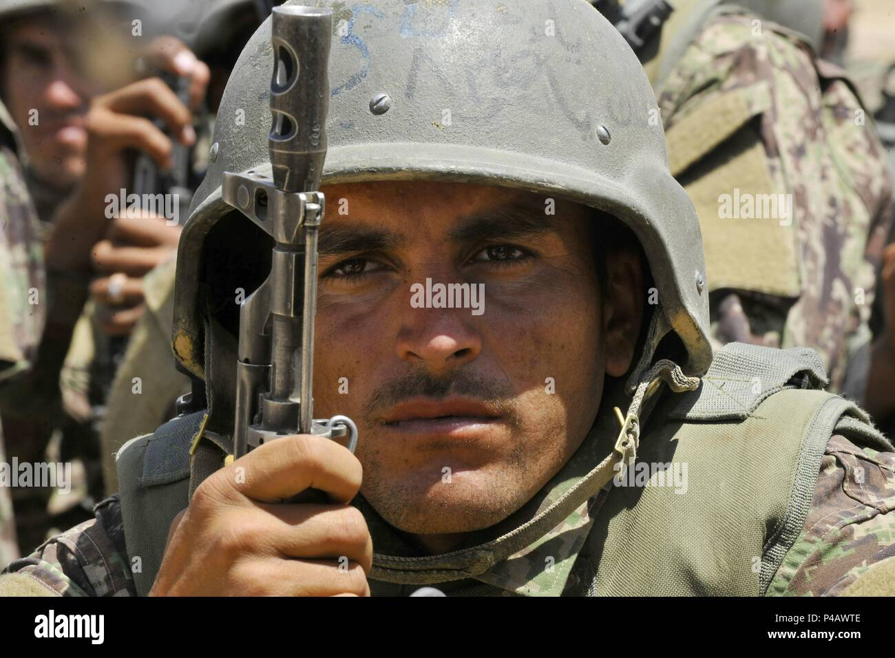 An Afghan National Army-Territorial Force member watches security demonstrations during an exercise at the Kabul Military Training Center in Kabul, Afghanistan, June 11, 2018, June 11, 2018. Demonstrations consisted of security checkpoint procedures, medical evacuations, Improvised Explosive Device detection, and concealment. (U.S. Air Force photo by Tech. Sgt. Sharida Jackson). () - Stock Image
