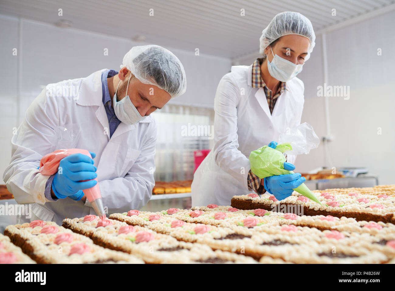 Process of cakes decorating on factory - Stock Image