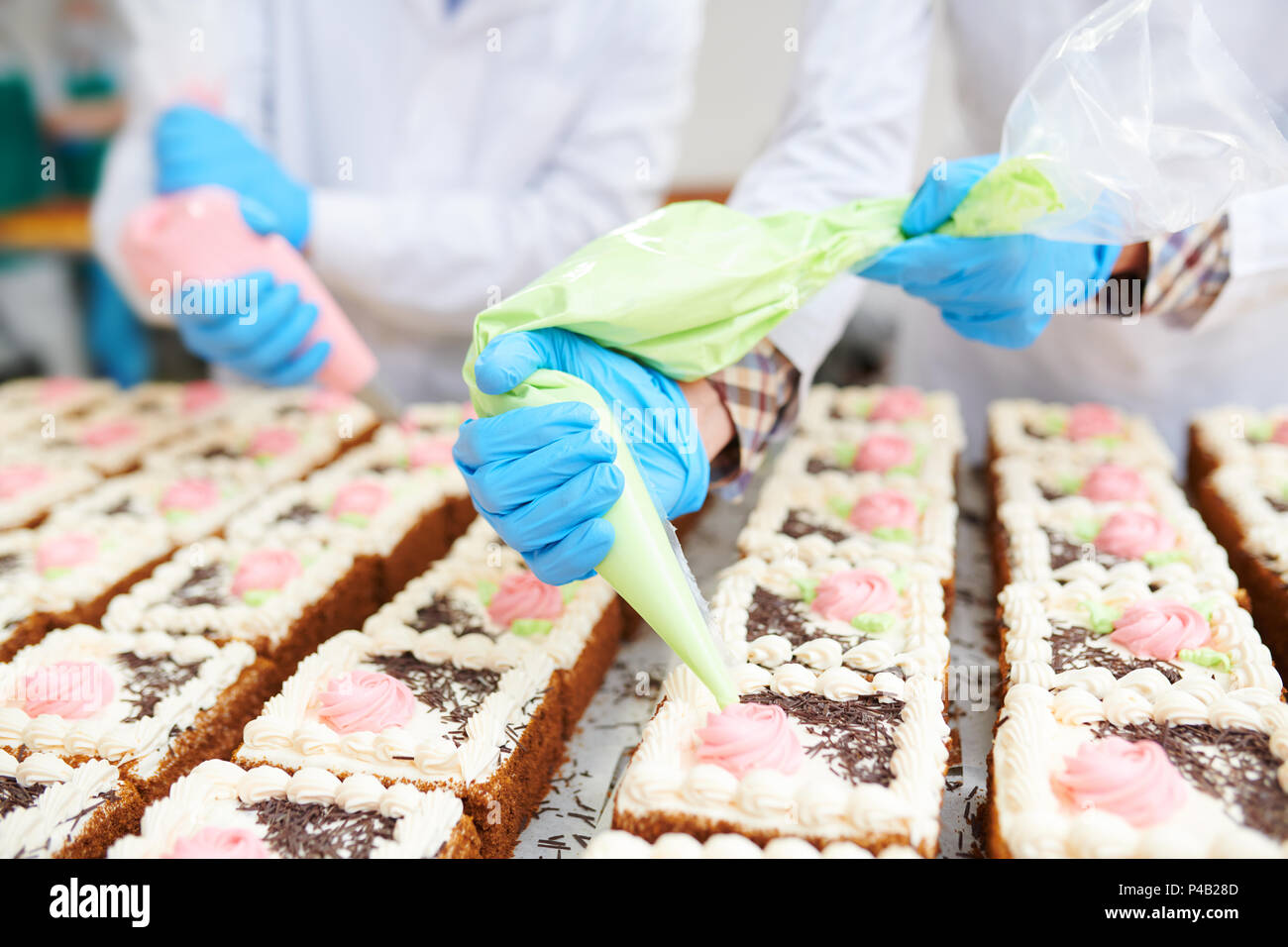 Cakes decorating in confectionery factory Stock Photo