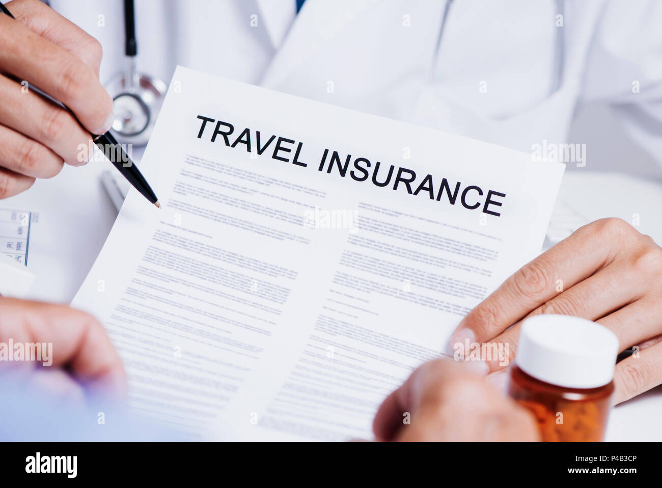 closeup of a caucasian doctor man, in a white coat, showing the clauses of a travel insurance policy to a senior caucasian man, sitting both at his de - Stock Image