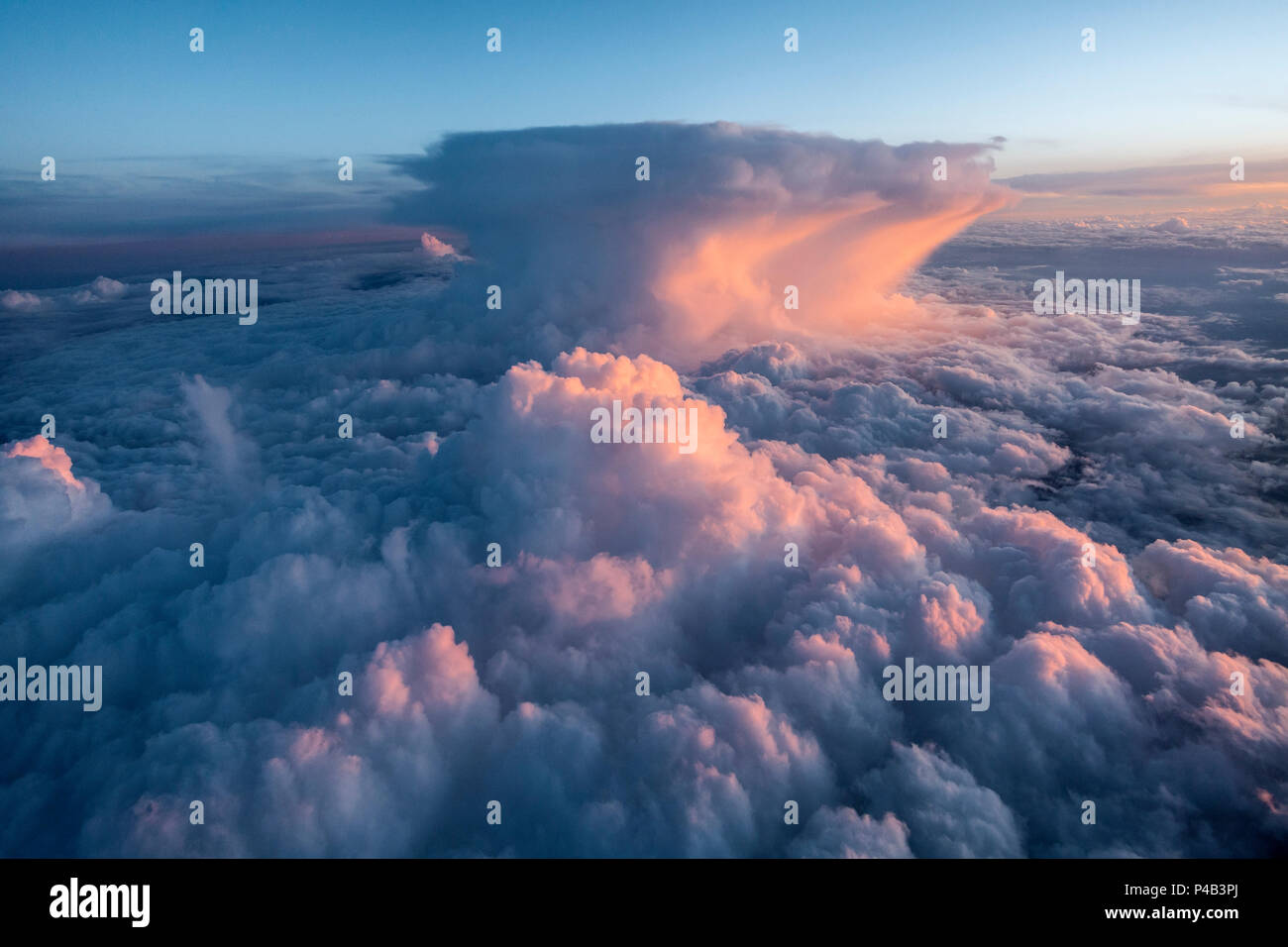 Summer storm clouds seen outside passenger airplane window at sunset, Orlando, Florida - Stock Image