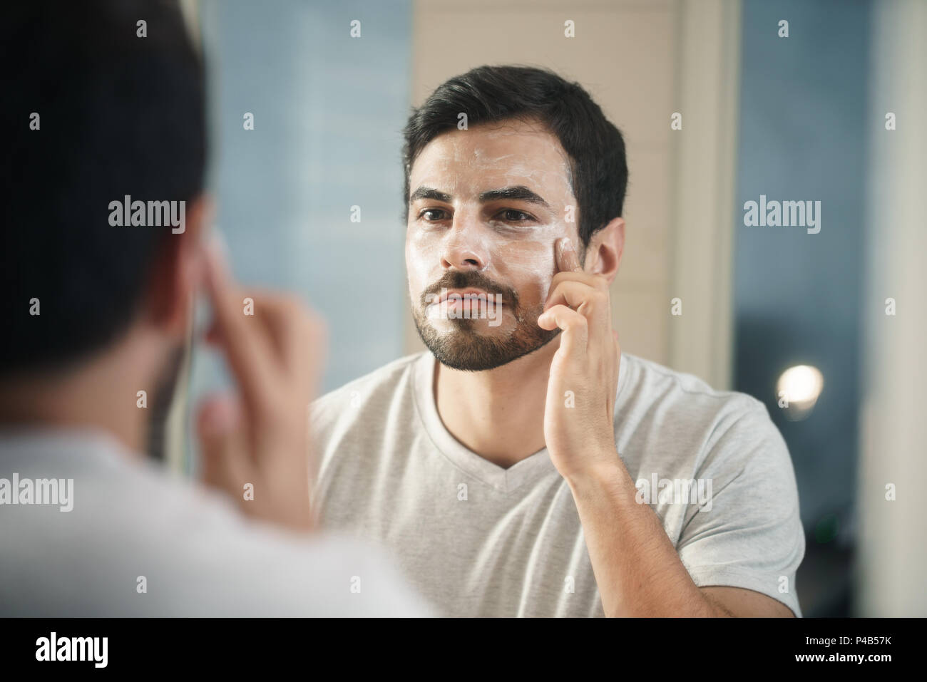 Young hispanic people and male beauty. Metrosexual man applying lotion for anti-aging treatment around eye - Stock Image