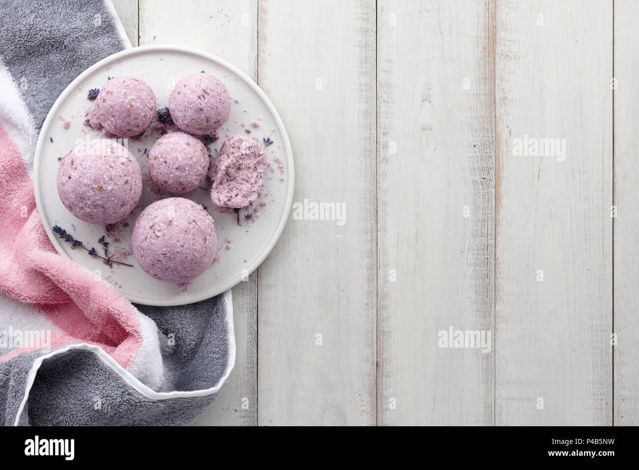 Handmade lavender bath bombs with towel on white planks - Stock Image