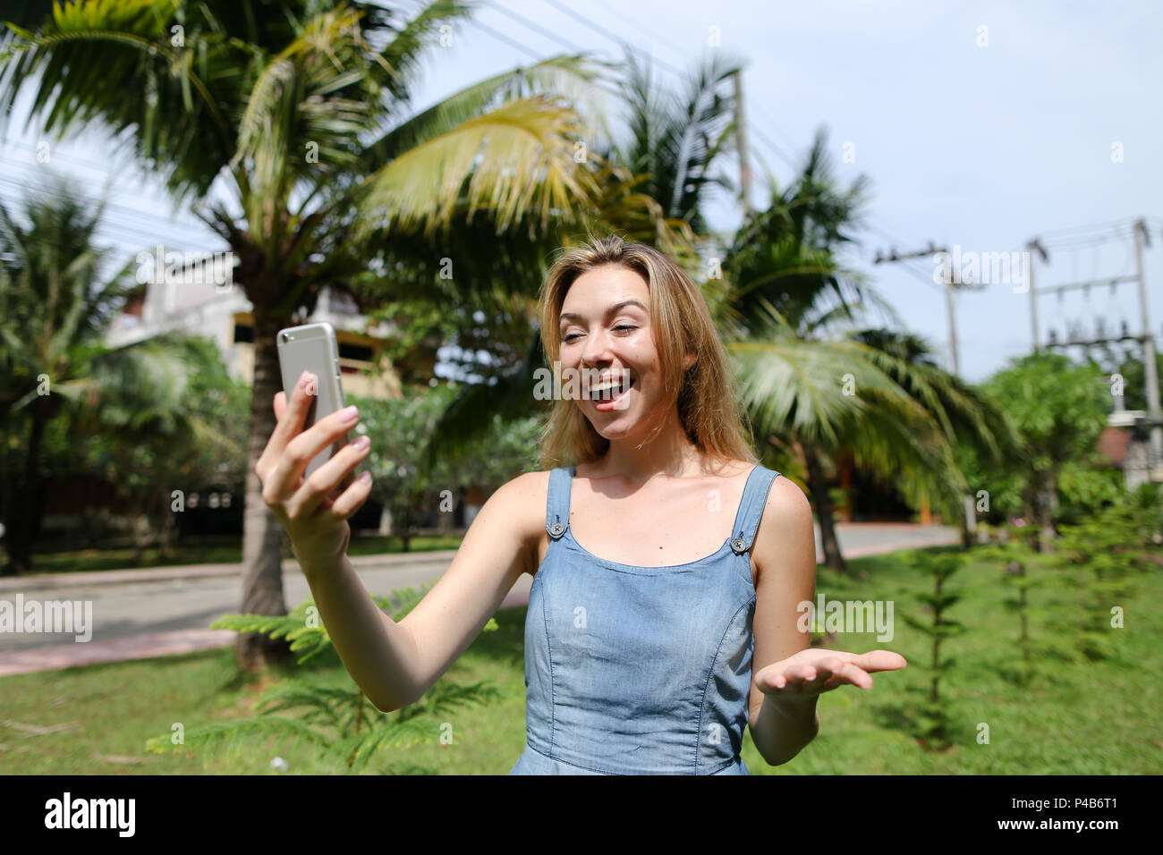 Young caucasian girl making selfie by smarthone near palm trees in background. - Stock Image