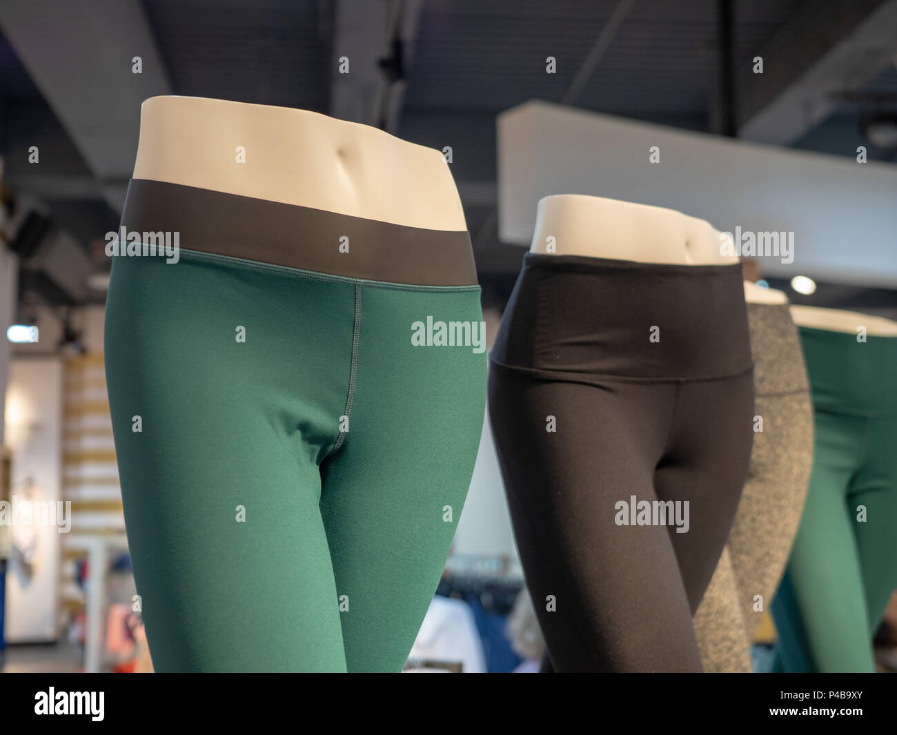 Plastic athletic mannequin lower bodies posing with yoga pants in a store - Stock Image