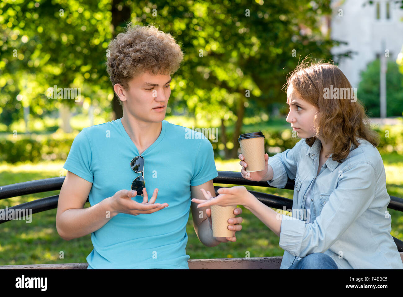A guy with a girl summer a park in nature. He holds cups with coffee and tea in his hands. Hands gesture misunderstanding of communication. The concept of talking to each other. Claim of resentment. - Stock Image