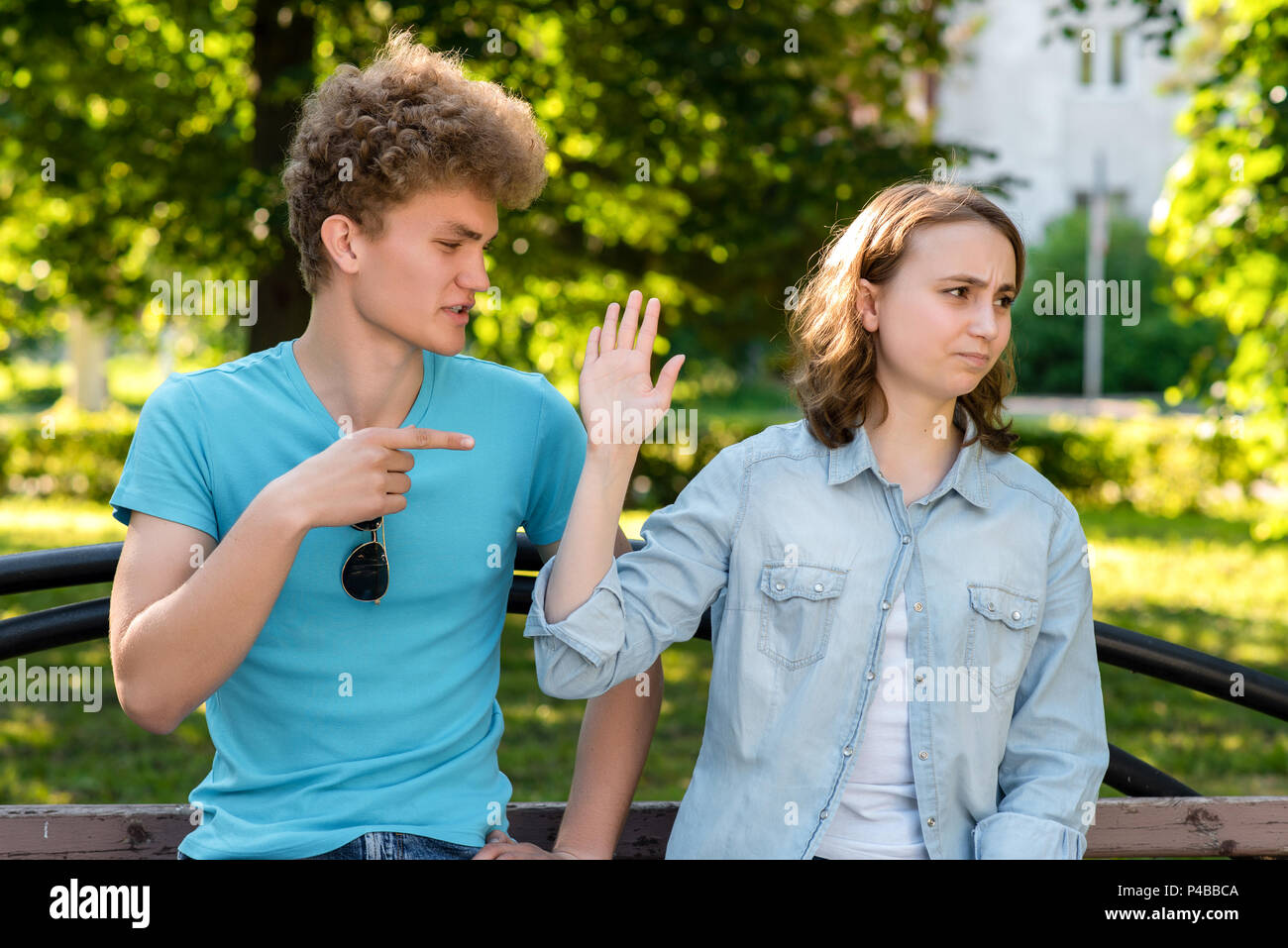 Young married couple. In summer in the park in nature. The guy scolds the girl. Emotions of mistrust. Insults and insults in the relationship. Problems in family life. Concept scandal behavior. - Stock Image