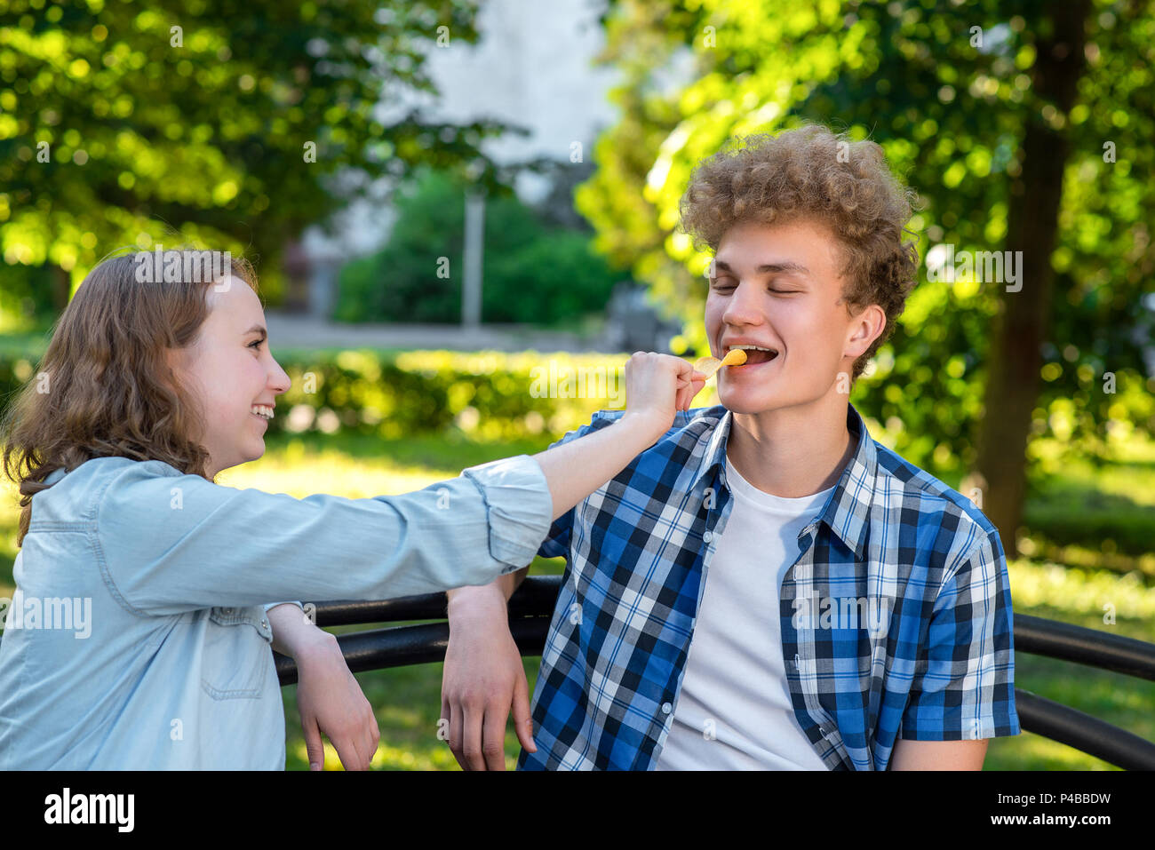 Young couple in love. Summer in park sit on a bench. A girl is feeding a guy with food. The guy smiles happily. The concept of a happy relationship. Stock Photo