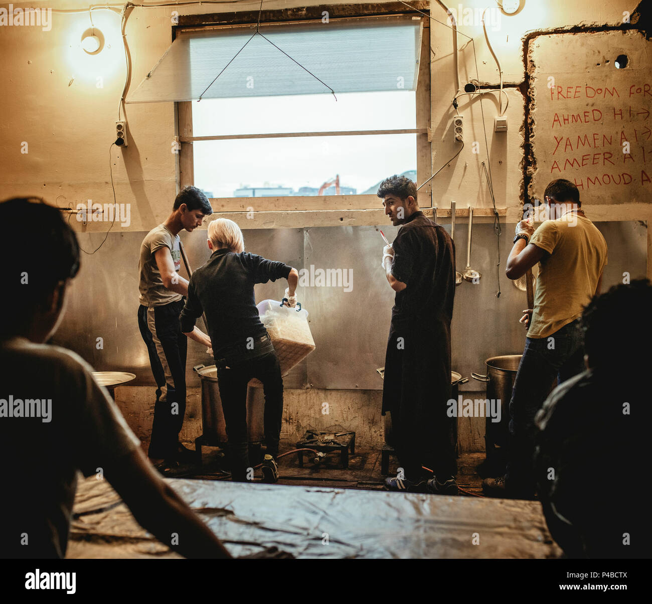 Volunteers of No Name Kitchen working in and around the warehouses in Belgrade. They organize food, clothes, firewood together with the refugees living there since 8 months, coming from all over the world. Sandra Latre, from Barcelona, cooking in the No Name Kitchen, set up by spanish volunteers in February 2017. It is working every day, they are cooking together with the refugees and give a second hot meal per day. 450 meals per day. Sandra decided to volunteer and contacted Soul Welders. - Stock Image