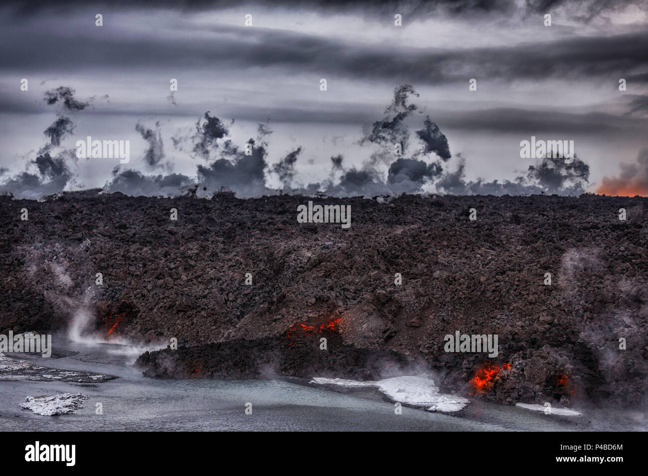 Hot lava steaming. Eruption site at Holuhraun near Bardarbunga Volcano, Iceland. August 29, 2014 a fissure eruption started in Holuhraun at the northern end of a magma intrusion, which had moved progressively north, from the Bardarbunga volcano. Bardarbunga is a stratovolcano located under Vatnajokull, Iceland's most extensive glacier. Picture Date: Oct 30, 2014 - Stock Image