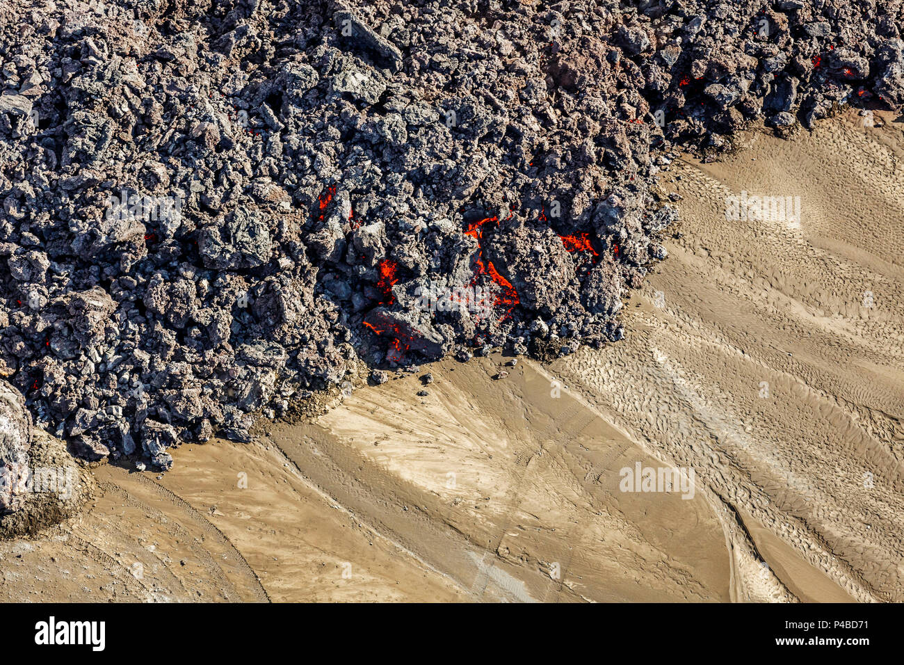 Hot lava creeping by tire tracks. Eruption site at Holuhraun near Bardarbunga Volcano, Iceland. August 29, 2014 a fissure eruption started in Holuhraun at the northern end of a magma intrusion, which had moved progressively north, from the Bardarbunga volcano. . Picture Date-Sept. 3, 2014 - Stock Image