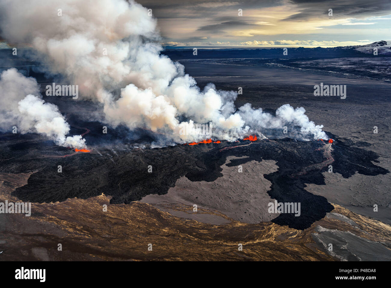 Lava and plumes from the Holuhraun Fissure by the Bardarbunga Volcano, Iceland. Sept. 1, 2014 Aerial view of the eruption at the Holuhraun Fissure by the Bardarbunga Volcano, Iceland. Looking South East with the Kverkfjoll mountain range in the distance. Dust storms result from the Hurricane Cristobal in the South Atlantic. On August 29, 2014, a fissure eruption started in Holuhraun at the northern end of a magma intrusion that had moved progressively north, from the Bardarbunga volcano. Bardarbunga is a stratovolcano located under Vatnajokull, Icelands most extensive glacier. - Stock Image