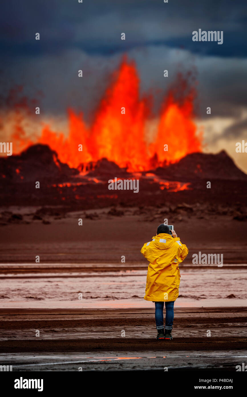 Woman taking pictures with a tablet at the volcano eruption at the Holuhraun fissure, by the Bardarbunga Volcano, Iceland. August 29, 2014 a fissure eruption started in Holuhraun at the northern end of a magma intrusion, which had moved progressively north, from the Bardarbunga volcano. . Picture Date-Sept. 1, 2014 - Stock Image