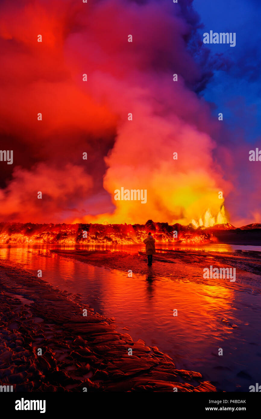 Woman watching the lava flow at the Holuhraun Fissure eruption near Bardarbunga Volcano, Iceland August 29, 2014, a fissure eruption started in Holuhraun at the northern end of a magma intrusion that had moved progressively north, from the Bardarbunga volcano.. Bardarbunga is a stratovolcano located under Vatnajokull, Icelands most extensive glacier. Picture Date-Sept 2, 2014 - Stock Image