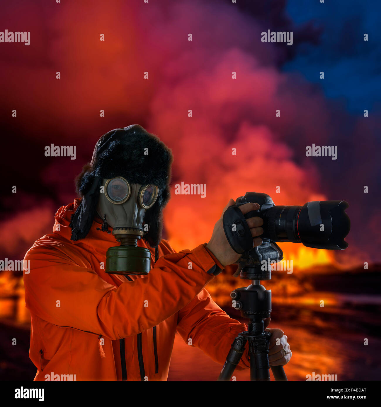 Photographer wearing a gas mask in front of glowing lava. Holuhraun, Bardarbunga Volcano eruption, Iceland - Stock Image
