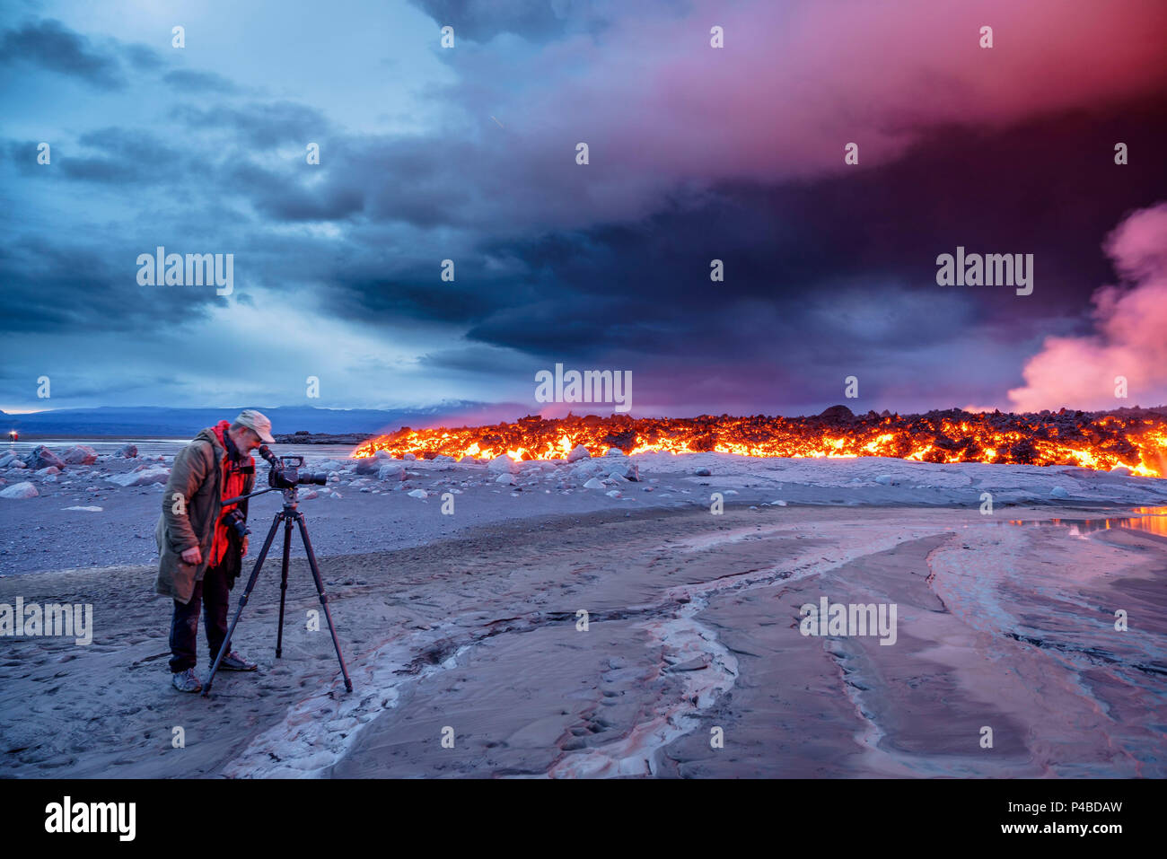 Photographer filming the volcano eruption at the Holuhraun Fissure, near the Bardarbunga Volcano, Iceland. August 29, 2014 a fissure eruption started in Holuhraun at the northern end of a magma intrusion, which had moved progressively north, from the Bardarbunga volcano, Picture Date-Sept. 2, 2014 - Stock Image