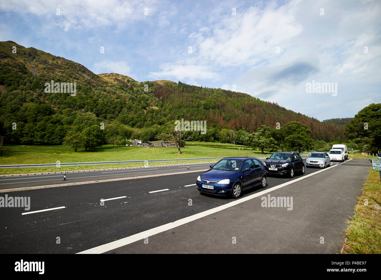 cars parked in a lay-by of the A66 on Bassenthwaite lake at blackstock point in the lake district Cumbria England UK - Stock Image