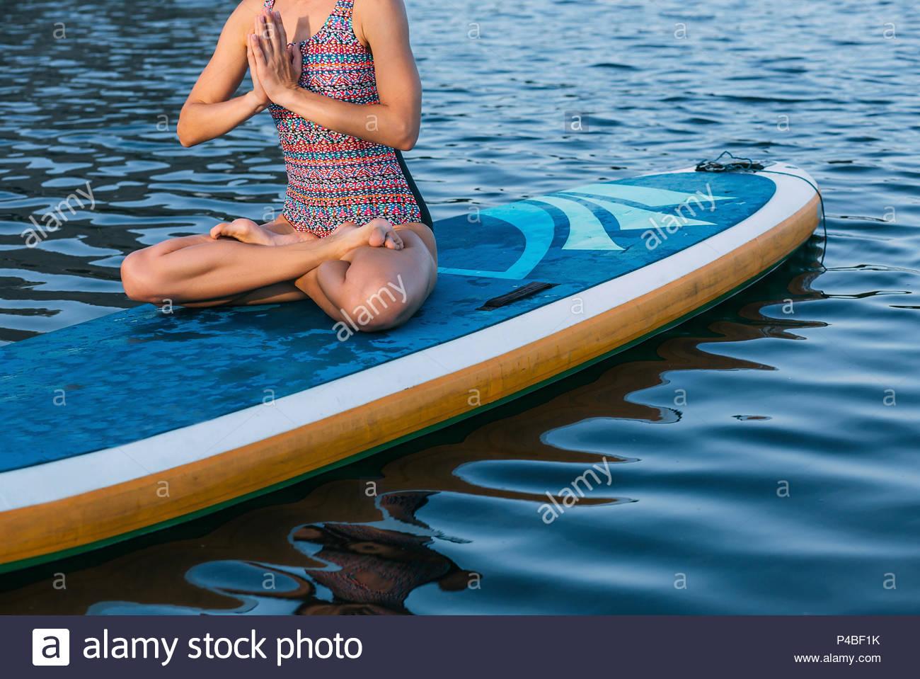 woman doing yoga on sup board - Stock Image