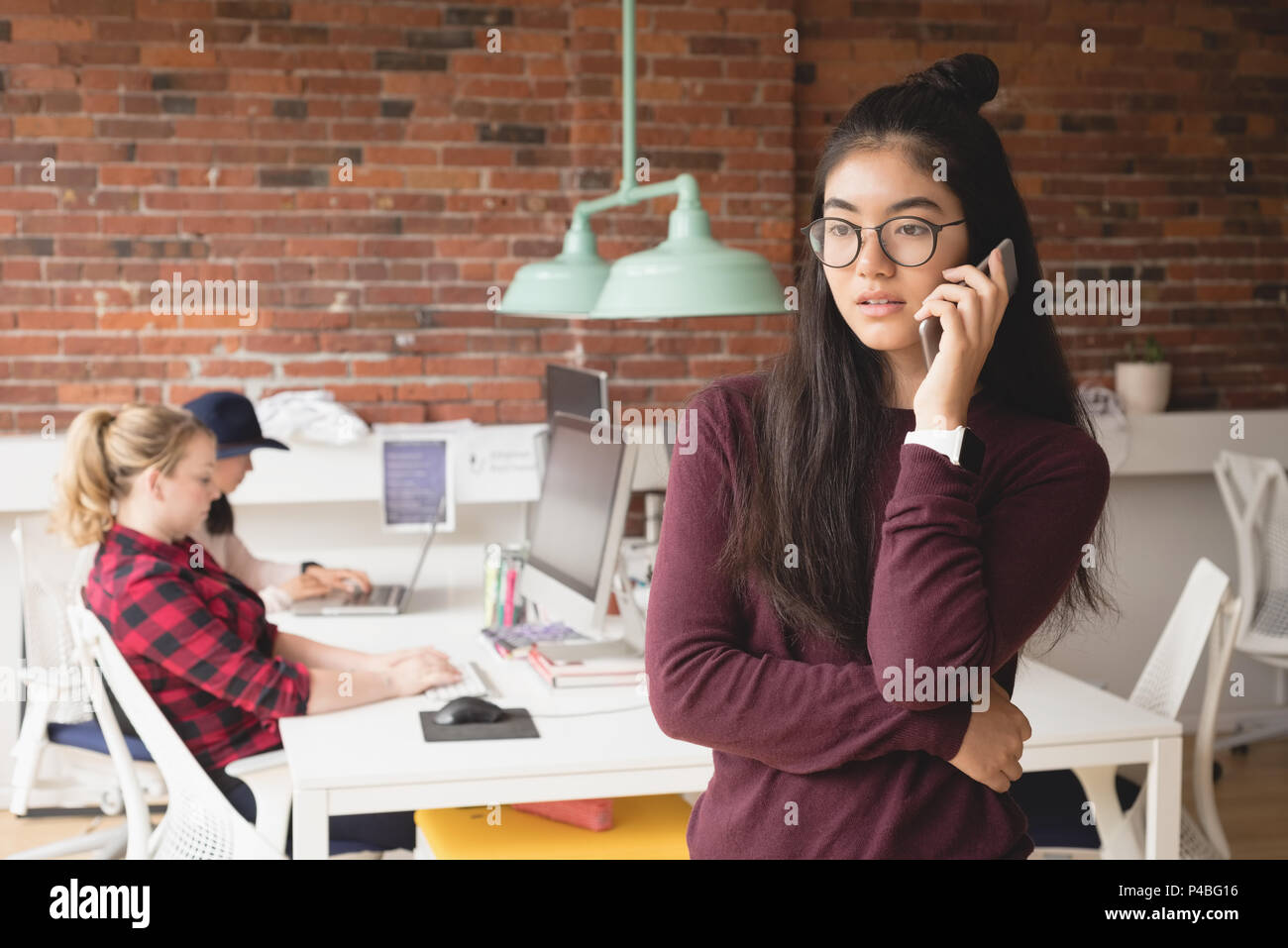 Female executive talking on mobile phone while colleagues working in background - Stock Image