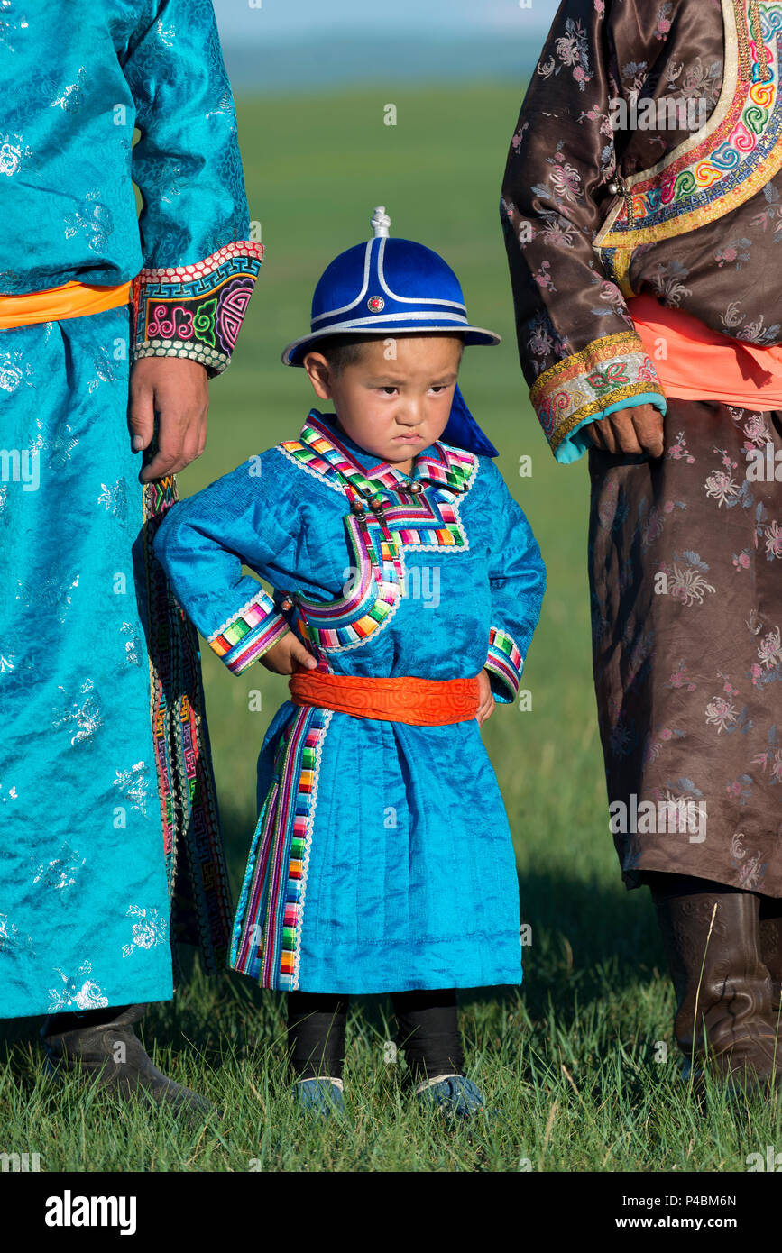 Wearing traditional Mongolian dress, a young boy pridefully stands with older family members, Xilinhot, Inner Mongolia, China - Stock Image