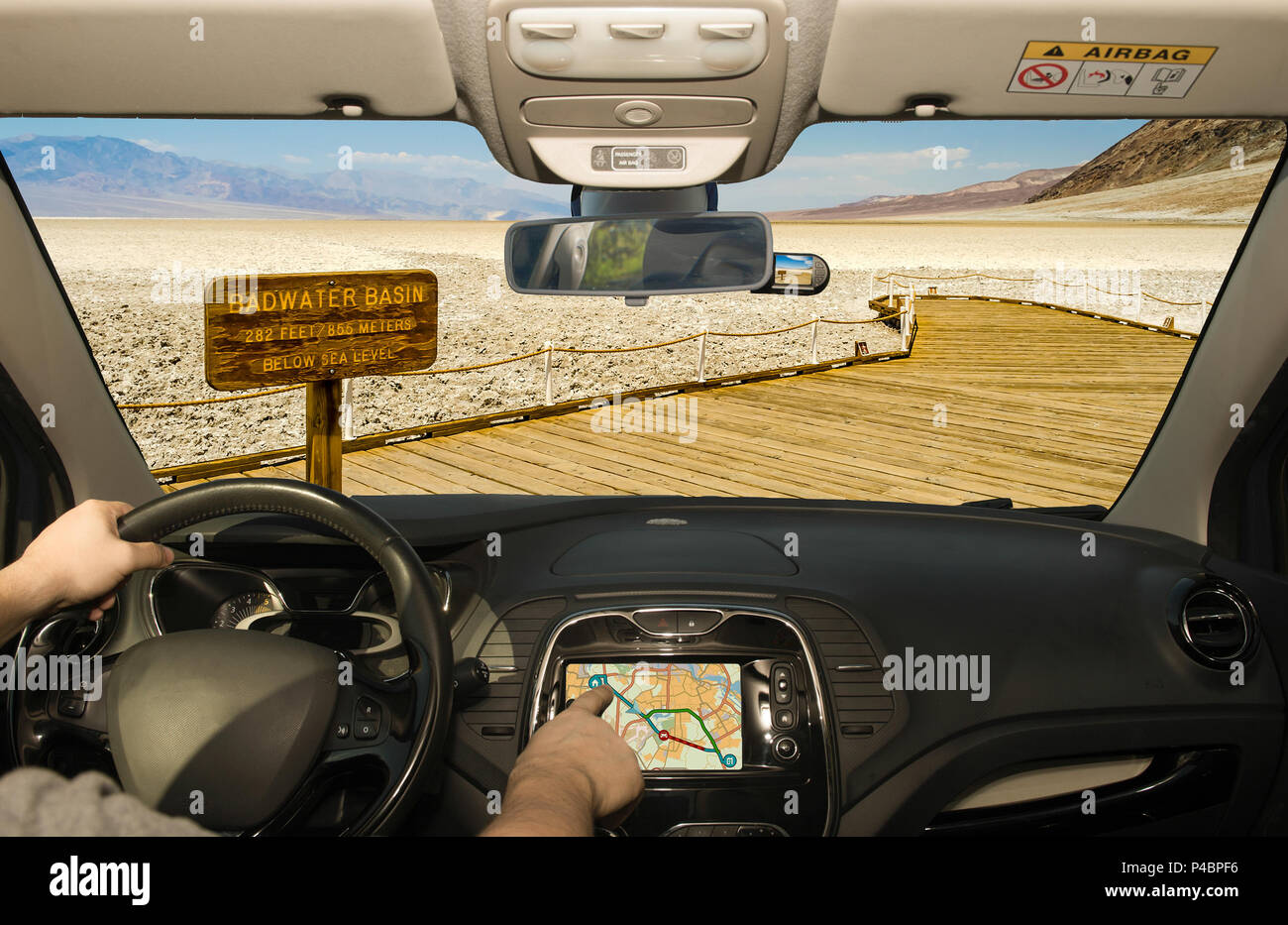 Driving a car while using the touch screen of a GPS navigation system in Badwater Basin, the lowest elevation point in USA, Death Valley National park - Stock Image