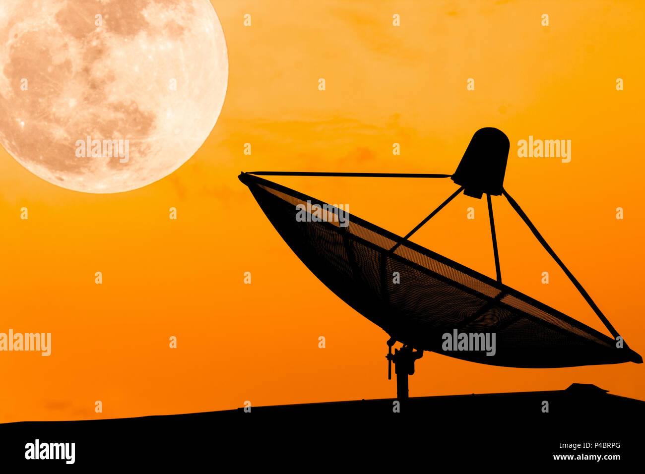 Communication satellite dish on the roof with supermoon sky background, twilight time, silhouette orange background, effect light, with copy space. Stock Photo