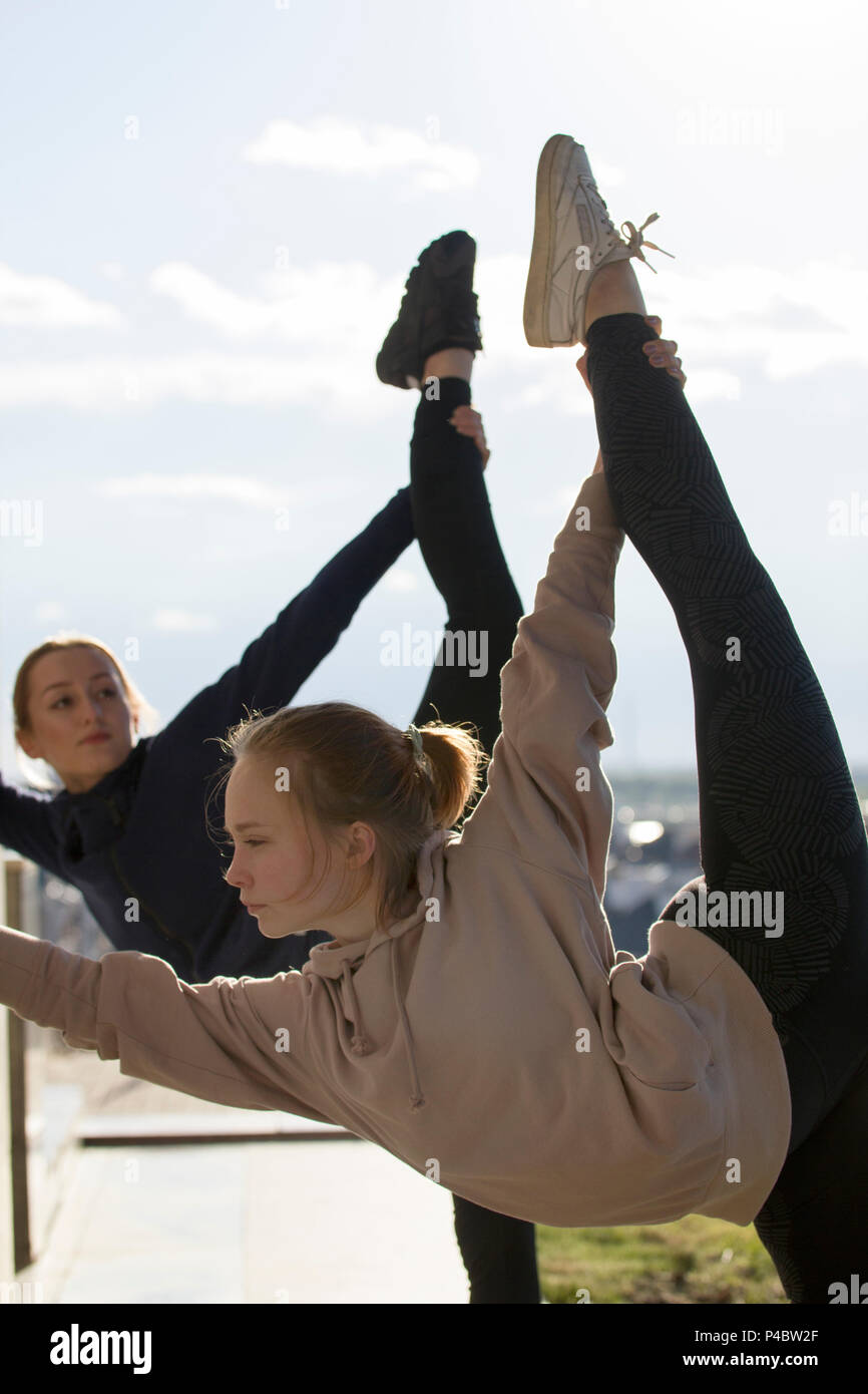 Two young attractive women doing acrobatics with cityscape on background - Stock Image