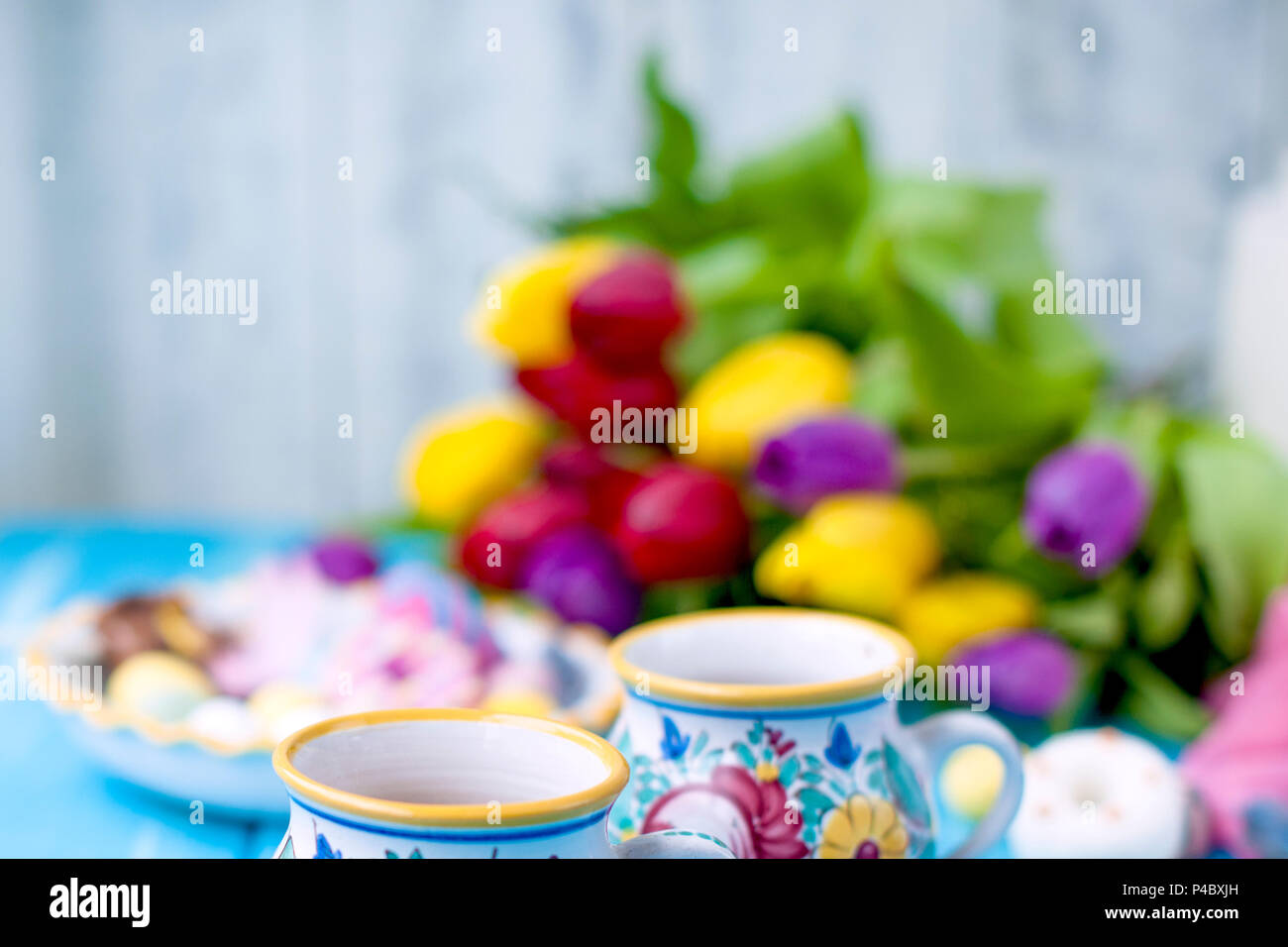 Easter sweets for the holiday. Spring. Bright colors on coffee mugs. A bouquet of fresh tulips. Free space for text . - Stock Image